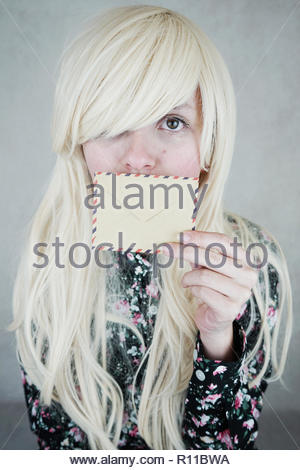 Portrait of a beautiful blonde woman holding an envelope - Stock Photo
