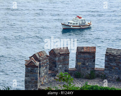 View from the fortress wall of a small boat on the sea surface. Part of the tower of the famous castle Rumeli Hisari on the Bosphorus, Istanbul - Stock Photo