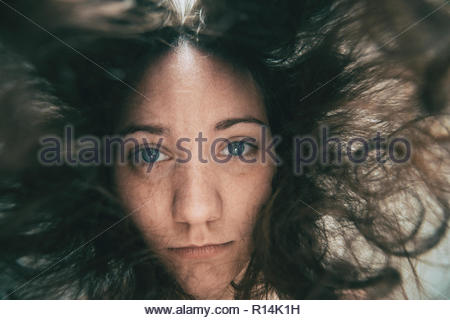 Low view shot of a woman looking into the camera under water - Stock Photo