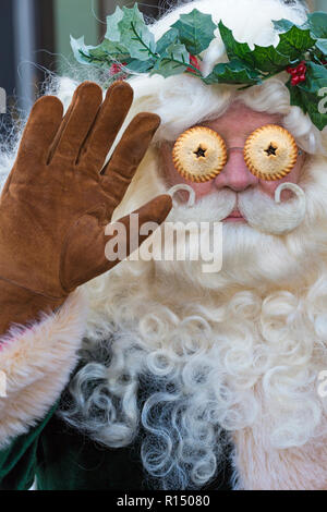 Santa Claus dressed in green Victorian Father Christmas costume at Victorian Festival of Christmas with mince pies as eyes - surreal surrealism - Stock Photo