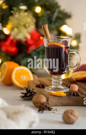 Winter composition. Mulled wine in glass on wood board at white background. Fir wreath, bells, tinsel and garlands, napkin, orange, cinnamon and spice - Stock Photo
