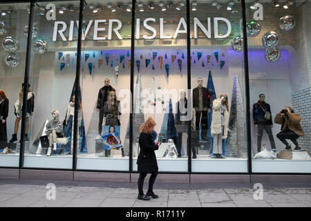 Shoppers are seen outside River Island store on London's Oxford Street. The retail sector faces difficulties as consumers cut down on spending and do more of their shopping online. A report by accountancy firm PWC has said that over 1,000 stores disappeared from Britain's top 500 high streets in the first six months of the year. - Stock Photo