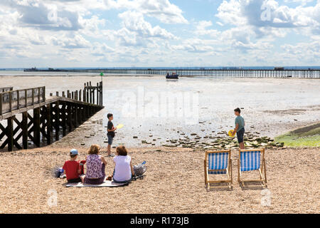 Family relaxing on Jubilee Beach, Southend-on-Sea, with Southend Pier in the distance - Stock Photo