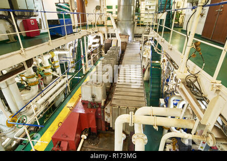 Panoramic view of main engine on a merchant ship in the engine room with all the piping, generators, turbins, etc. - Stock Photo