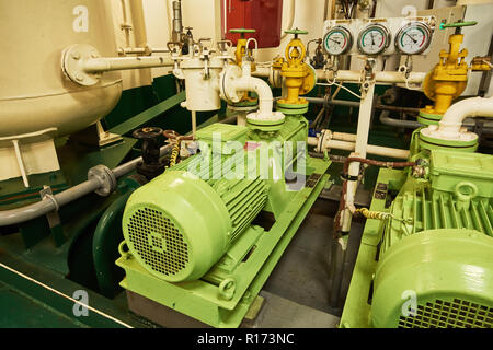 Panoramic view of electric motors on a merchant ship in the engine room with all the piping, generators, turbins, etc. - Stock Photo