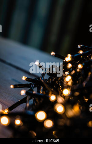 Christmas fairy lights wrapped around card on a wooden table at night - Stock Photo