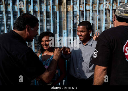 Tijuana, Baja California, Mexico. November 11, 2018 - GUILLERMO NAVARRETE, left, a pastor of the El Faro Border Church, congratulates KARLA LINDO, 27, and REYNALDO HERNANDEZ, 27, both recent migrants from Honduras, at U.S.-Mexico border after leading their marriage ceremony at Playas de Tijuana in Tijuana, Baja California. The couple, who are expecting a baby, requested asylum into the Unites States shortly after arriving to Tijuana on October 25th. According to the couple, they have since received a confirmation notice from immigration officials and are currently waiting for the request to be - Stock Photo
