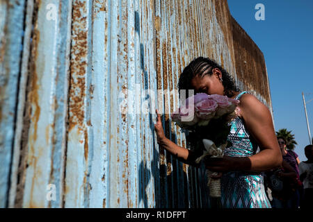 Tijuana, Baja California, Mexico. November 11, 2018 - KARLA LINDO, 27, a recent migrant from Honduras, touches the U.S.-Mexico border after getting married to REYNALDO HERNANDEZ, 27, also a migrant from Honduras, at Playas de Tijuana in Tijuana, Baja California. The couple, who are expecting a baby, requested asylum into the Unites States shortly after arriving to Tijuana on October 25th. According to the couple, they have since received a confirmation notice from immigration officials and are currently waiting for the request to be fully processed. Credit: Joel Angel Juarez/ZUMA Wire/Alamy Li - Stock Photo