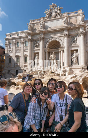 Tourists taking a group selfie photograph in front of the Trevi Fountain,  Rome, Italy. - Stock Photo