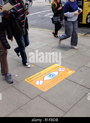 Street pavement signs asking pedestrians to take care crossing the road and not look at their phones for listen to music on headphones in Brighton UK - Stock Photo