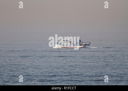 Matosinhos, Portugal - September 29, 2015: Taditional portuguese sardine fishing wooden trawler sailing towards Leixoes harbor in a misty morning. - Stock Photo