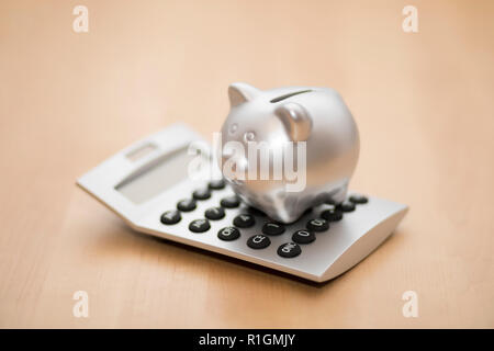 Piggy bank on calculator. Saving, accounting or banking concept. - Stock Photo