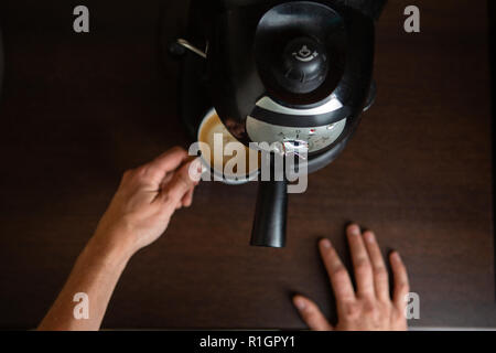 Photo of coffee maker, hands of man pouring coffee in mug - Stock Photo