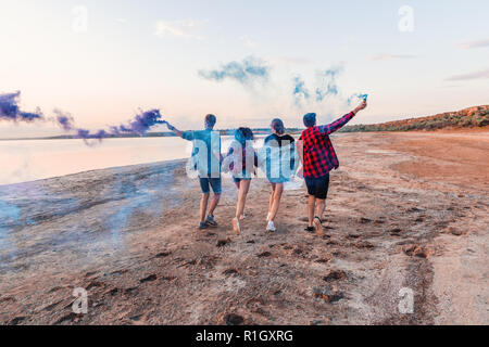 young friends running with hand flare or fusee - Stock Photo
