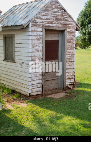 An old weathered tool shed with a tin roof on a rural farm in Oklahoma, USA. - Stock Photo