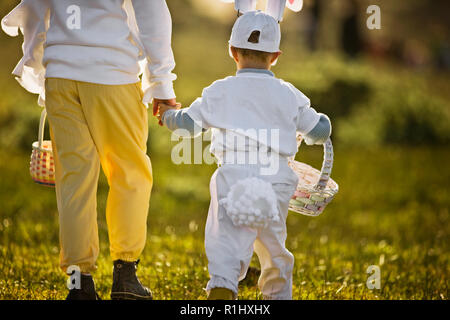Two brothers in Easter costumes on an Easter egg hunt - Stock Photo