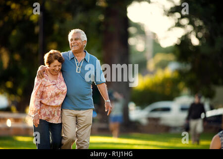 Smiling mature couple walking through a park. - Stock Photo