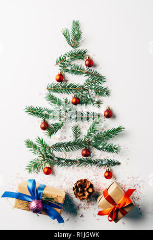 top view of green pine branch decorated as festive christmas tree with gifts and glitters on white background - Stock Photo