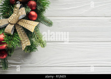 top view of wreath with red christmas toys on white wooden surface - Stock Photo