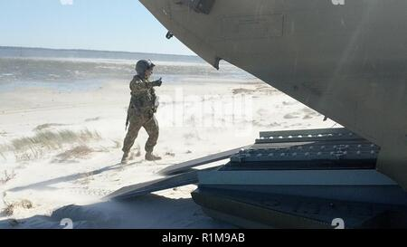 A CH-47 Chinook crewmember from the New York Army National Guard's Company B, 3rd Battalion, 126th Aviation assists with the offload of rescue personnel and vehicles October 13 near Alligator Point, a barrier island off Apalachicola Bay, Florida following the impact of Hurricane Michael. The New York Army National Guard crews deployed 11 personnel and two aircraft to support the Florida Guard's 1st Battalion, 111th Aviation Task Force. Crews flew for three days, transporting 32, 240 pounds of cargo before returning to their flight facility in Rochester, N.Y. October 17. - Stock Photo