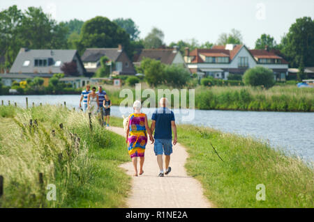 Elderly couple and a family walking along side de canal de Eem in Baarn and enjoying a warm summer day, the Netherlands - Stock Photo