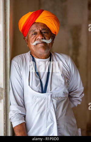Portrait of a Rajasthani gentleman with impressive moustache dressed in a traditional Kurta with saffron turban in Jodhpur palace, India - Stock Photo