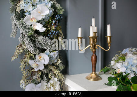 Candlestick with candles on a white fireplace with flowers and fir branches, decorated for Christmas. Christmas morning. Holiday mood. - Stock Photo