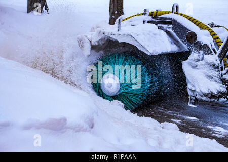 Snow-removing machine removes snow from city streets 2018 - Stock Photo