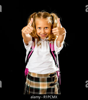 Pretty cute blonde hair girl with a pink schoolbag looking at camera showing thumb up gesture happy to go to school isolated on black background in ba - Stock Photo