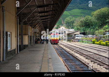 Nanu-Oya to Ella train arriving. Considered to be one of the most conic railway journeys in the world. Red & yellow carriage waits at the platform. - Stock Photo