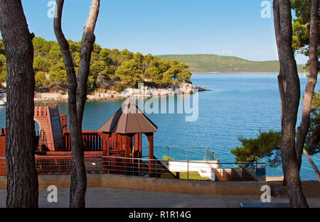 Brown playground near deep blue sea and rocky coast with green forest, pine trees and hills on the back. Bozava, Croatia, summer - Stock Photo