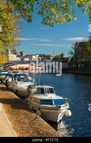 Pleasure boats moored along the River Ouse and asunlit autumn leaves in October 2018 - Stock Photo