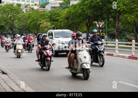 Street scene with people riding motorbikes and scooters on a busy city road. Hanoi, Vietnam, Asia - Stock Photo