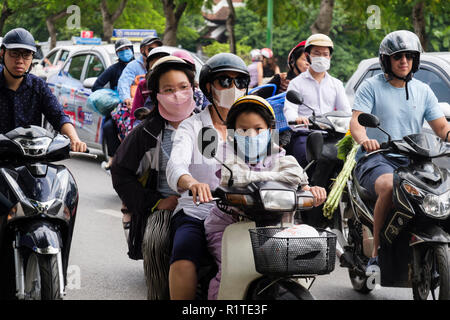Street scene with people wearing face masks on motorbikes and scooters to protect against air pollution on a busy urban road. Hanoi, Vietnam, Asia - Stock Photo