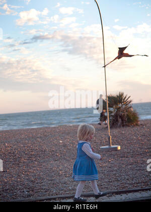 A small girl in a pretty blue dress walks along the edge of the beach at Brighton - Stock Photo