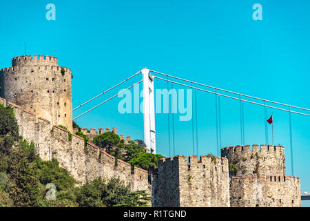 Rumeli Hisari fortress on the Bosporus, with the western part of the Fatih Sultan Mehmet Bridge connecting Europe and Asia - Stock Photo
