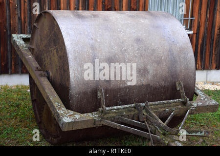 metal farm roller rural scene background, old and rusty metal farm roller made of heavy iron - Stock Photo