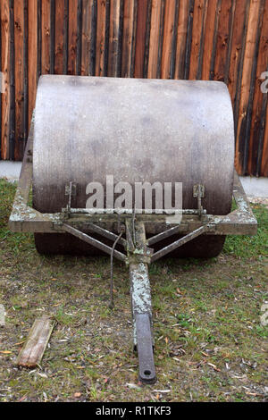 old and rusty metal farm roller made of heavy iron, front view of a metal farm roller - Stock Photo
