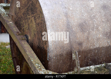 side view of a metal farm roller, old and rusty metal farm roller made of heavy iron - Stock Photo