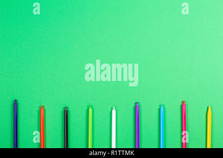 Set of colored pens on green background - Stock Photo