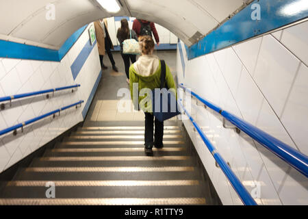 Tube commuters time, Young woman walking down on stairs to the tube station - Stock Photo