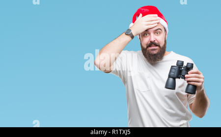 Young caucasian hipster man wearing christmas hat looking though binoculars over isolated background stressed with hand on head, shocked with shame an - Stock Photo