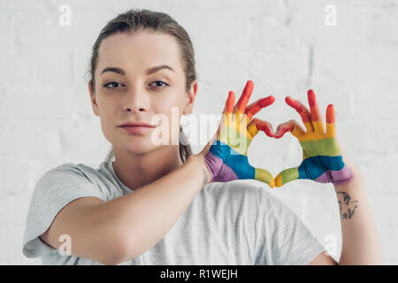 young transgender man making heart sign with hands in colors of pride flag in front of white brick wall - Stock Photo