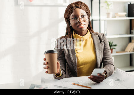 african american female architect in glasses holding coffee to go, using smartphone and working at desk on project with blueprints - Stock Photo