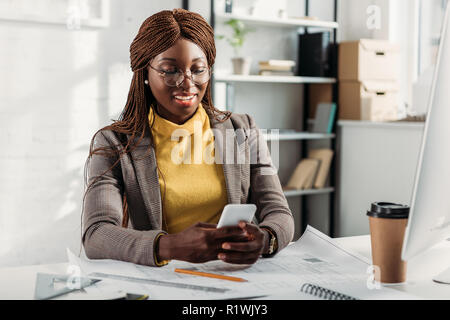 smiling african american female architect in glasses using smartphone and working at desk with blueprints in office - Stock Photo