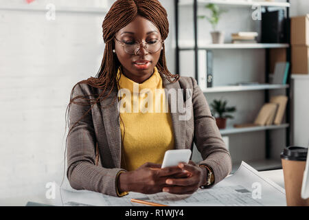 beautiful african american female architect in glassses using smartphone and working at desk with blueprints in office - Stock Photo