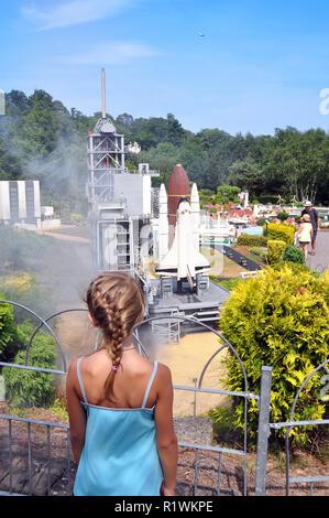 Editorial - LEGO miniland in Legoland Windsor theme park. Girl is enjoying the Nasa rocket launch in Lego. - Stock Photo