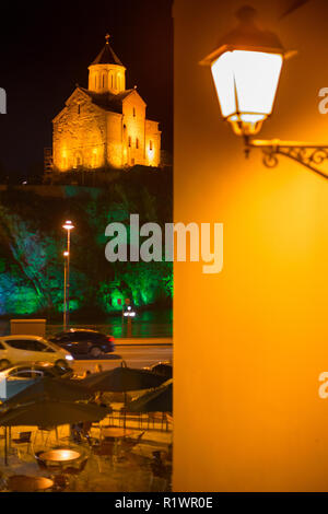 Metekhi church are seen with retro design lantern in the background. Tbilisi, Georgia - Stock Photo