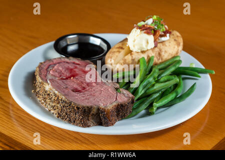 prime rib meal served on a plate with a loaded potato and green beans with a side of a jus - Stock Photo