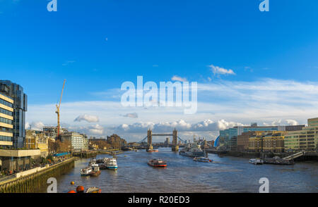 View from London Bridge of the River Thames and the Pool of London to Tower Bridge and HMS Belfast moored by Hays Galleria on a sunny day in winter - Stock Photo